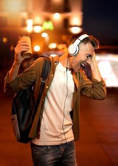 Retrato de um homem sorridente na cidade à noite com fones de ouvido e uma xícara de café