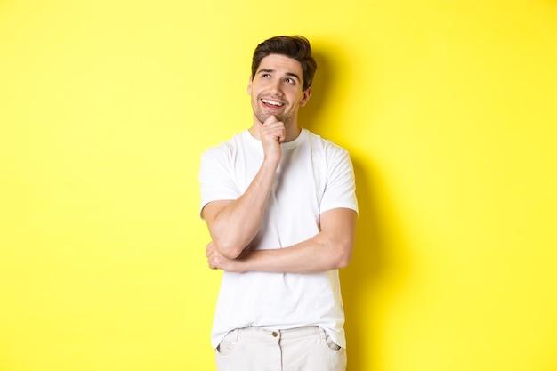 Retrato de um homem sorridente, olhando pensativo no canto superior esquerdo, escolhendo algo, ter uma ideia, em pé contra um fundo amarelo.