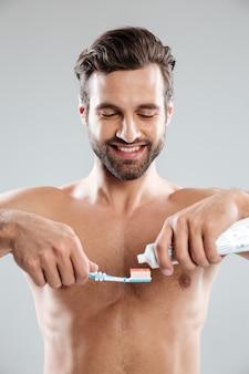 Retrato, de, um, homem sorridente, pôr, creme dental, escova um