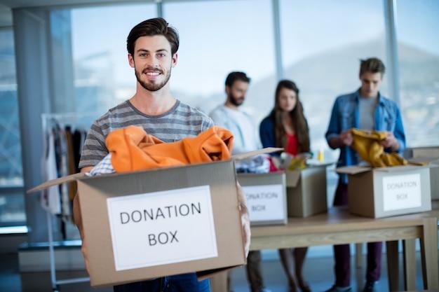 Retrato de um homem sorridente segurando uma caixa de doações no escritório