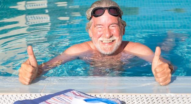 Retrato de um homem sorridente sênior, fazendo esporte na piscina. sol no rosto. estilo de vida saudável na aposentadoria