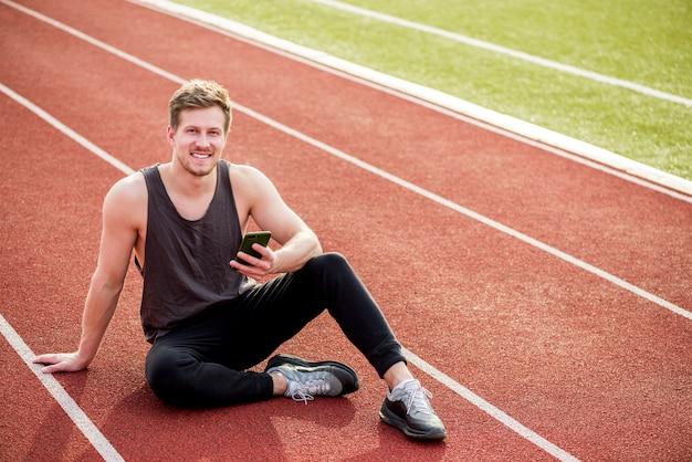 Retrato de um homem sorridente, sentado na pista de corrida vermelha, segurando o telefone celular na mão