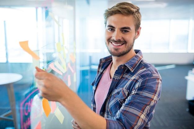 Retrato de um homem sorridente tocando nota adesiva na parede de vidro do escritório