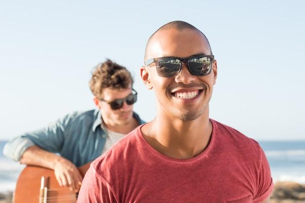 Retrato de um homem sorridente usando óculos escuros na frente de um homem tocando guitarra