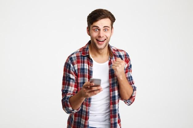 Retrato de um homem surpreendido feliz olhando segurando o telefone móvel