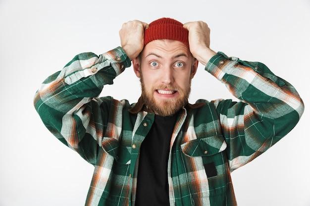 Retrato de um homem tenso, usando chapéu e camisa xadrez, gritando e agarrando a cabeça, em pé, isolado sobre um fundo branco