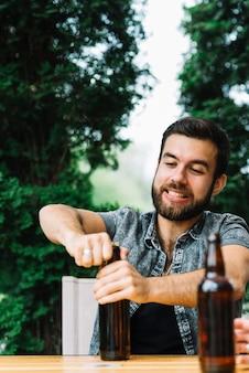 Retrato, de, um, homem, tentando, para, abrir, a, garrafa cerveja, boné
