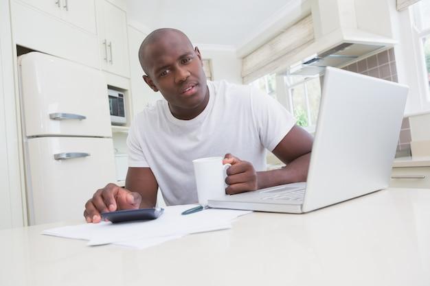 Retrato de um homem trabalhando e usando seu laptop e olhando a câmera