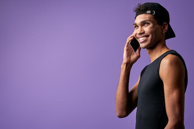 Retrato de um homem transgênero moreno falando no celular em uma camiseta preta e boné latino trans gênero