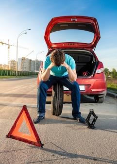Retrato de um homem triste sentado na roda sobressalente perto de um carro quebrado