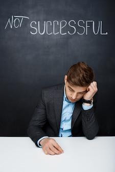 Retrato de um homem triste sobre o quadro negro com texto sem êxito
