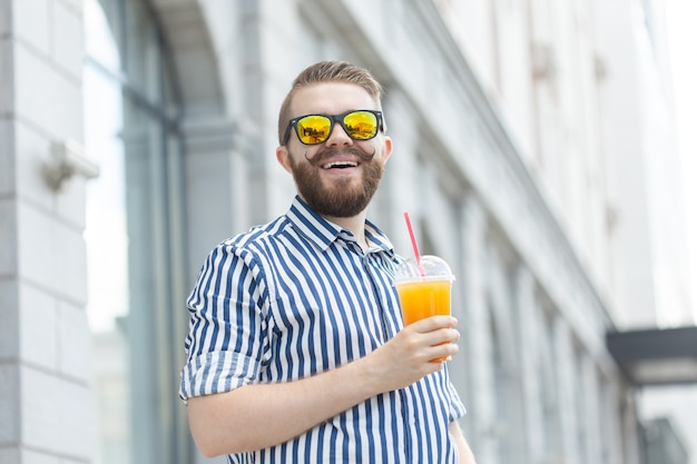 Retrato de um homem turva elegante jovem hippie com barba e bigode com suco de laranja fresco nas mãos. conceito de lanche saudável.