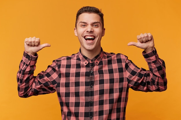 Retrato de um homem vaidoso e feliz em uma camisa jeans cerrando os punhos como vencedor e apontando para si mesmo com o polegar