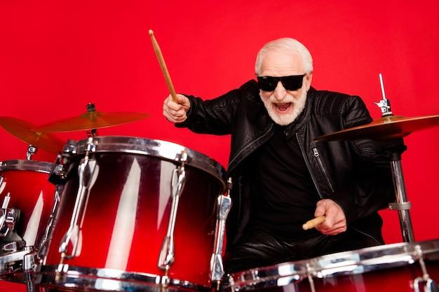 Retrato de um homem velho e louco, punk rocker tocar tambor, curtir a discoteca, festival de gravação, composição de estúdio, usar jaqueta de couro isolada sobre fundo de cor de brilho brilhante