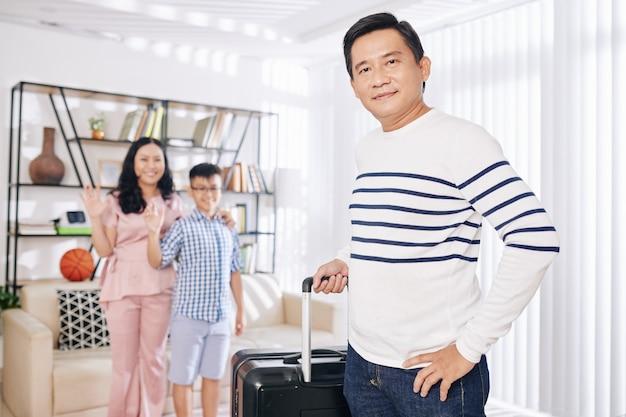 Retrato de um homem vietnamita maduro com uma mala saindo em uma viagem de negócios e sua família acenando para ele no fundo