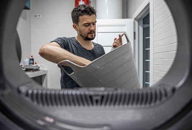 Retrato de um homem, vista da máquina de lavar, carregando e lavando a roupa suja.