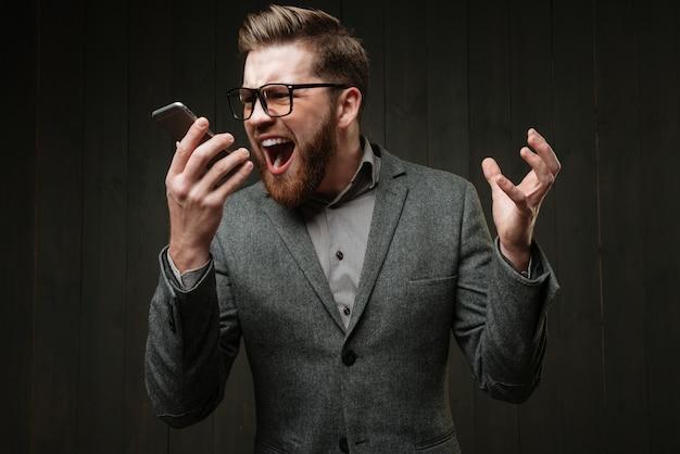 Retrato de um homem zangado em um terno casual gritando para o celular isolado no fundo preto de madeira