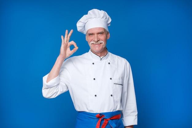 Retrato de um idoso chef isolado na parede azul, com um gesto de ok
