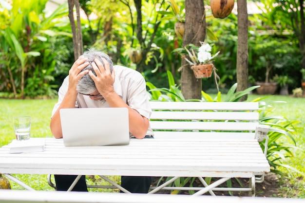 Retrato de um idoso idoso asiático segura a cabeça com a mão por causa de estresse após tentar usar um laptop de computador no quintal após se aposentar. conceito de ageism e hobbies após a aposentadoria.