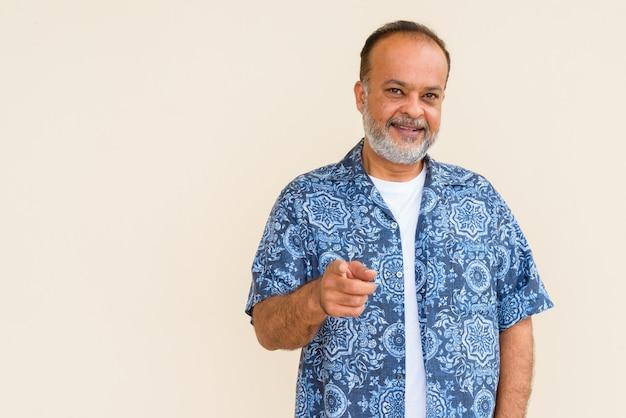 Retrato de um indiano barbudo feliz sorrindo contra uma parede simples