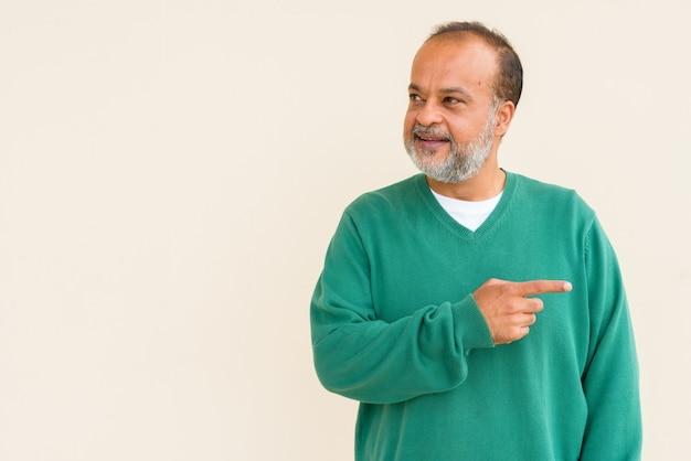 Retrato de um indiano bonito com barba grisalha contra uma parede simples