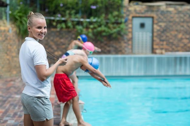 Retrato de um instrutor alegre monitorando o tempo à beira da piscina