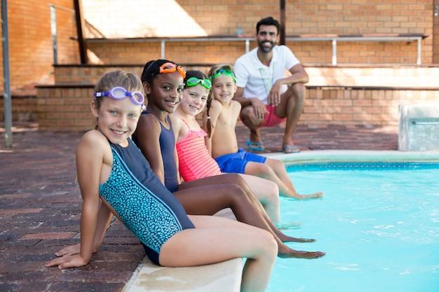 Retrato de um instrutor masculino feliz e crianças relaxando à beira da piscina