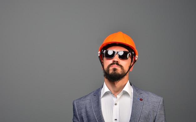 Retrato de um investidor imobiliário sério em óculos de sol e capacete de segurança