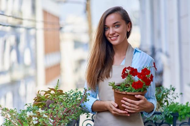 Retrato de um jardineiro feliz e sorridente mulher atraente usando avental segurando um vaso de flores em uma varanda