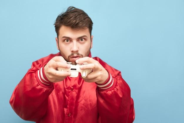Retrato de um jogador adulto emocional com um joystick na mão no azul