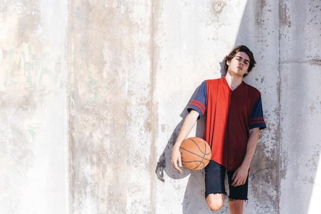 Retrato, de, um, jogador basquetebol, inclinar-se, parede
