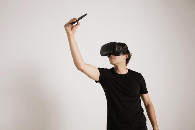 Retrato de um jogador com fone de ouvido de rv e camiseta preta em branco tirando uma selfie com seu smartphone