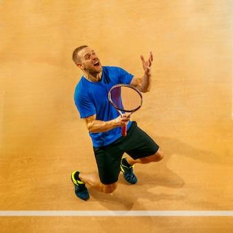 Retrato de um jogador de tênis bonito, celebrando seu sucesso em uma parede de quadra. emoções humanas, vencedor, esporte, conceito de vitória