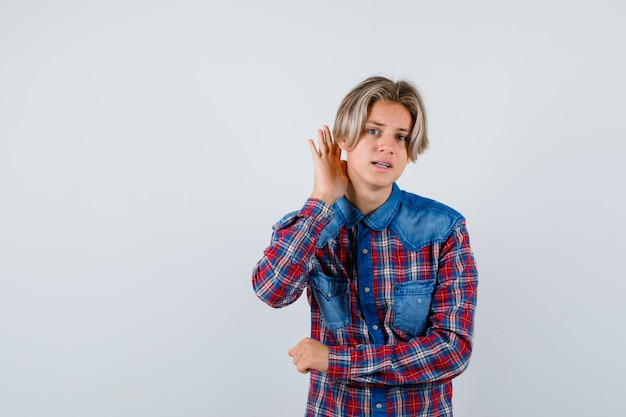 Retrato de um jovem adolescente com a mão atrás da orelha em uma camisa xadrez e olhando confuso com vista frontal
