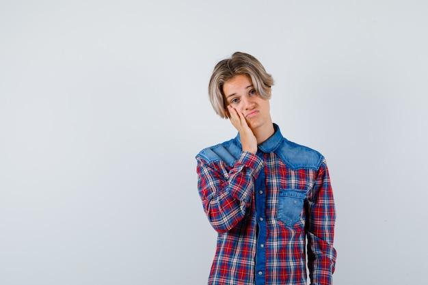 Retrato de um jovem adolescente com a mão na bochecha em uma camisa xadrez e olhando desapontado com a vista frontal