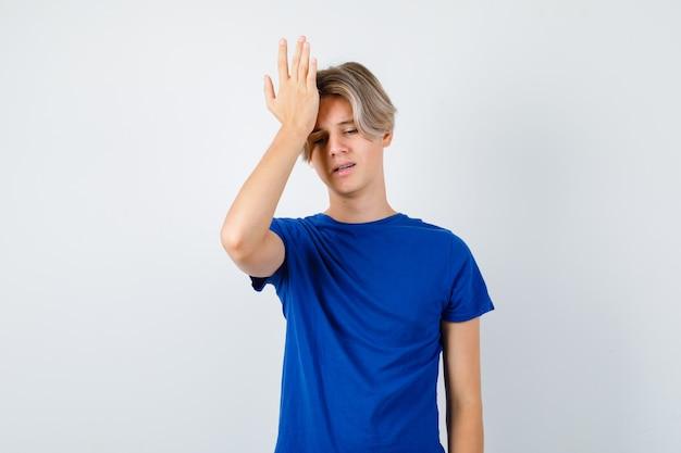Retrato de um jovem adolescente com a mão na testa em uma camiseta azul e olhando a vista frontal esquecida