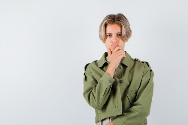 Retrato de um jovem adolescente com a mão no queixo com uma jaqueta verde e olhando a vista frontal mal-humorada