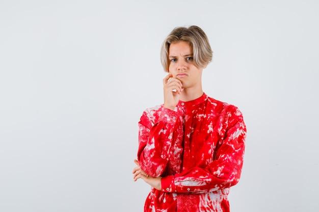 Retrato de um jovem adolescente com a mão no queixo na camisa e parecendo desapontado com a vista frontal