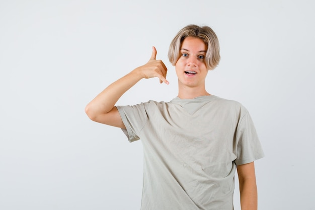 Retrato de um jovem adolescente mostrando um gesto de telefone em uma camiseta e olhando alegremente para a frente