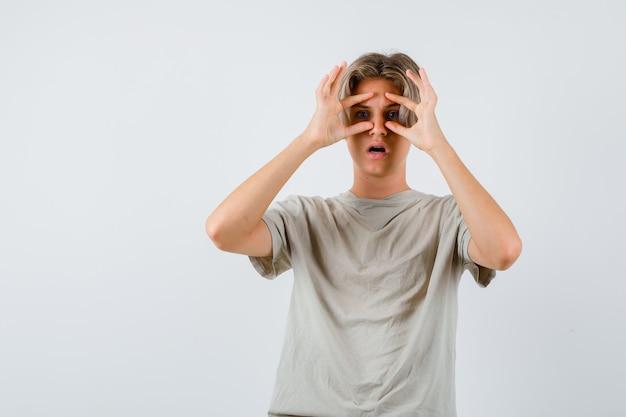 Retrato de um jovem adolescente olhando por entre os dedos em uma camiseta e olhando confuso de frente