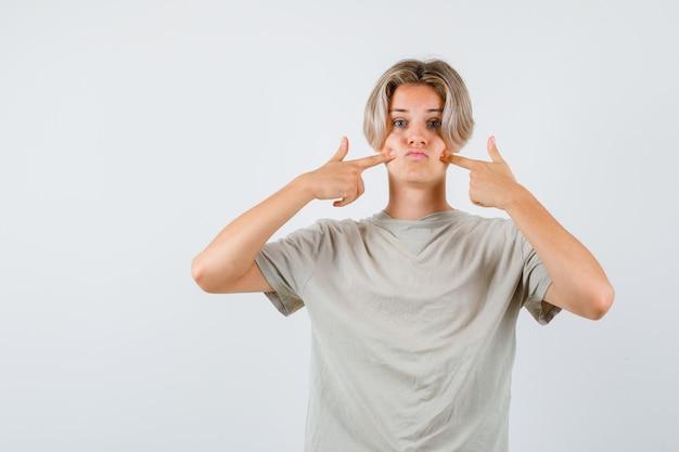 Retrato de um jovem adolescente pressionando os dedos nas bochechas inchadas em uma camiseta e parecendo perplexo com a vista frontal
