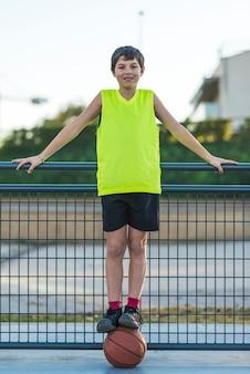 Retrato de um jovem adolescente vestindo uma bola de basquete amarela sem mangas e sorrindo