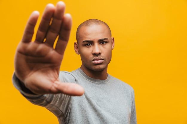 Retrato de um jovem africano atraente e confiante em pé sobre a parede amarela, mostrando um gesto de pare