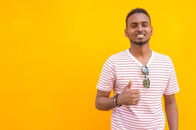 Retrato de um jovem africano bonito barbudo com cabelo afro contra uma parede amarela na rua ao ar livre