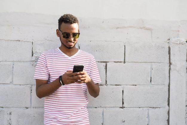 Retrato de um jovem africano bonito barbudo com cabelo afro contra uma parede de tijolos na rua ao ar livre