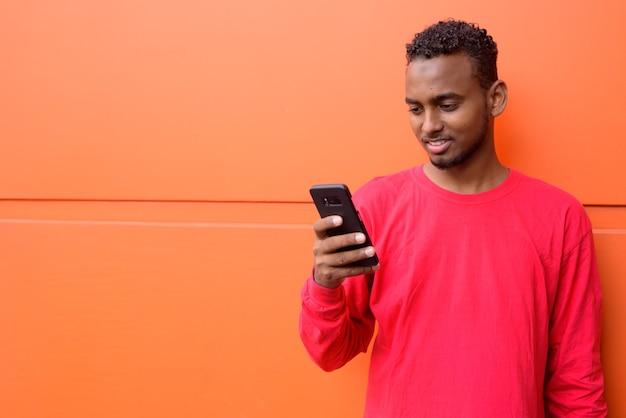 Retrato de um jovem africano bonito barbudo com cabelo afro contra uma parede laranja ao ar livre