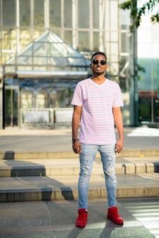Retrato de um jovem africano bonito, barbudo e cabelo afro, explorando as ruas da cidade ao ar livre