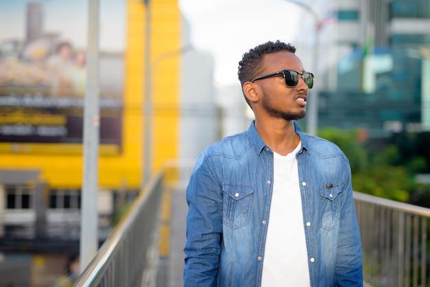 Retrato de um jovem africano bonito, barbudo e cabelo afro, na passarela ao ar livre da cidade