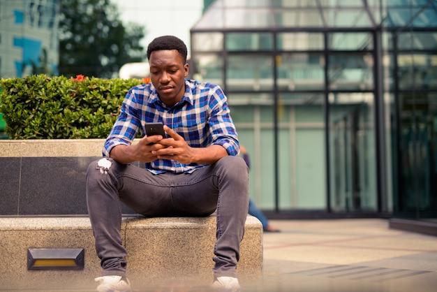 Retrato de um jovem africano bonito no parque ao ar livre da cidade
