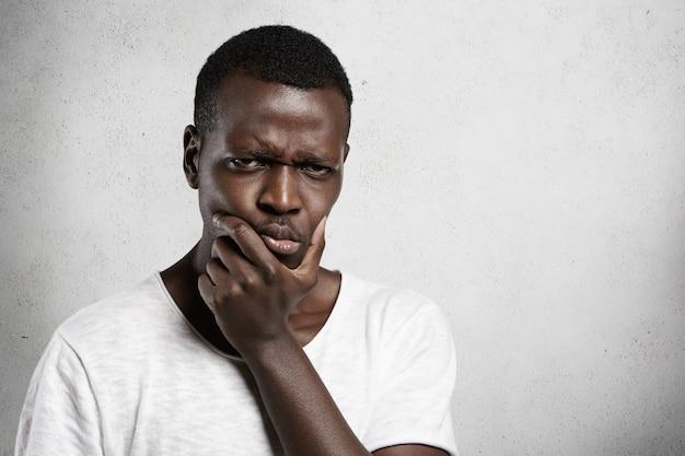 Retrato de um jovem africano cético olhando com expressão de suspeita ou aborrecido, segurando a mão no queixo, duvidando, pensando em algo.